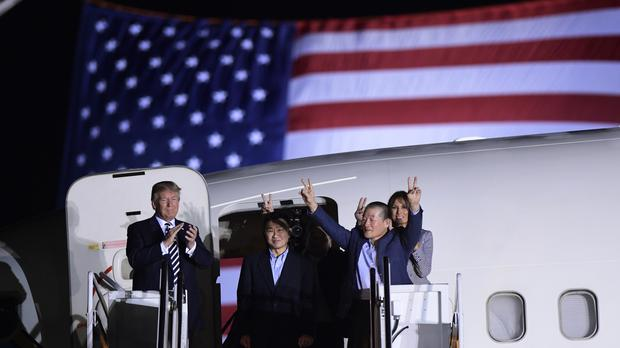 President Donald Trump greets Tony Kim, Kim Hak Song, seen in the shadow, and Kim Dong Chul (AP)