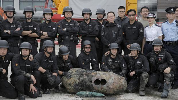 The police bomb squad pose with the deactivated bomb in Hong Kong (Kin Cheung/AP)