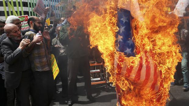 Iranian protesters burn a US flag during demonstrations in Tehran (Vahid Salemi/AP)