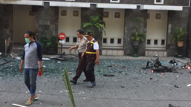 Officers walk past debris at Santa Maria church where an explosion went off in Surabaya, Indonesia (AP Photo/Trisnadi)