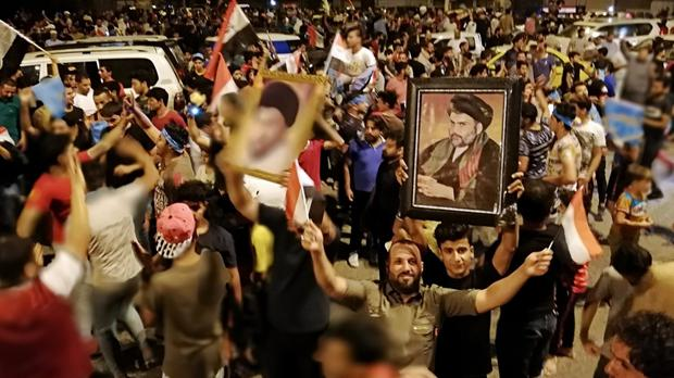 Followers of Shiite cleric Muqtada al-Sadr, seen in the posters, celebrate after the preliminary results of the parliamentary elections are announced (Hadi Mizban/AP)