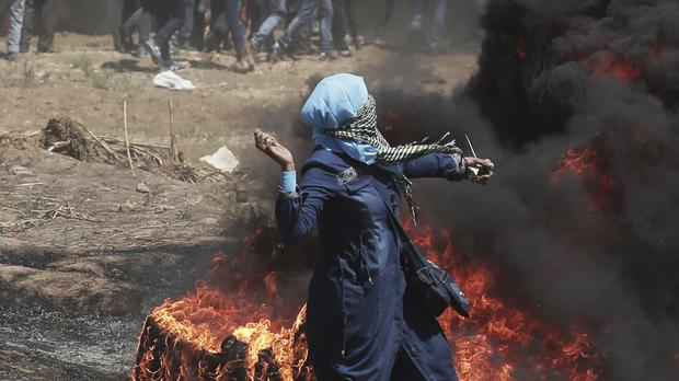 A Palestinian woman hurls stones towards Israeli troops (AP)