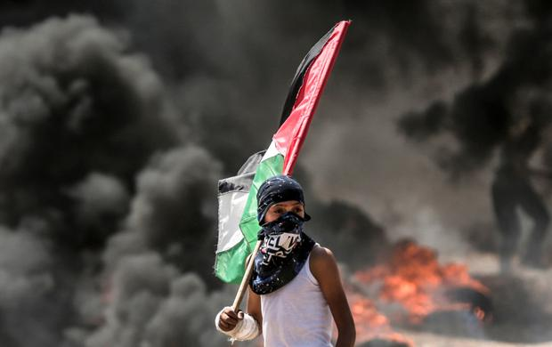 A Palestinian boy holding his national flag looks at clashes with Israeli security forces near the border. Photo: Getty