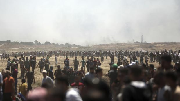 Palestinian protesters gathered during a protest at the Gaza Strip's border with Israel (AP Photo/Khalil Hamra)
