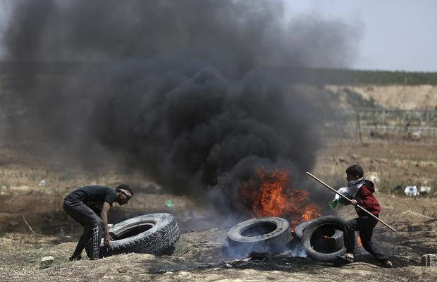 Palestinian protesters burn tyres during a protest at the Gaza Strip's border with Israel (AP Photo/Khalil Hamra)