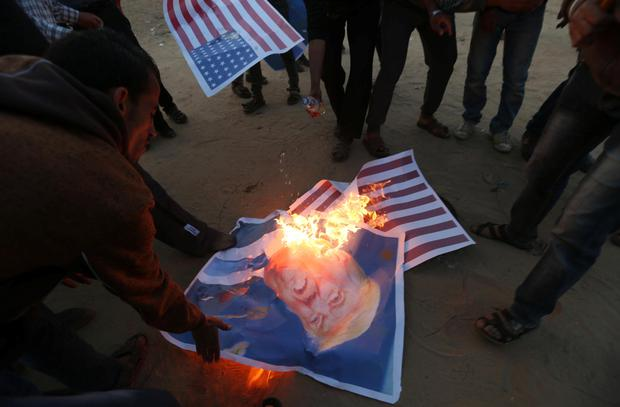Palestinian demonstrators burn representations of US flags. Photo: Reuters