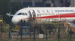 Workers inspect a Sichuan Airlines aircraft that made an emergency landing after a windshield on the cockpit broke off, at an airport in Chengdu, Sichuan province. Photo: Reuters
