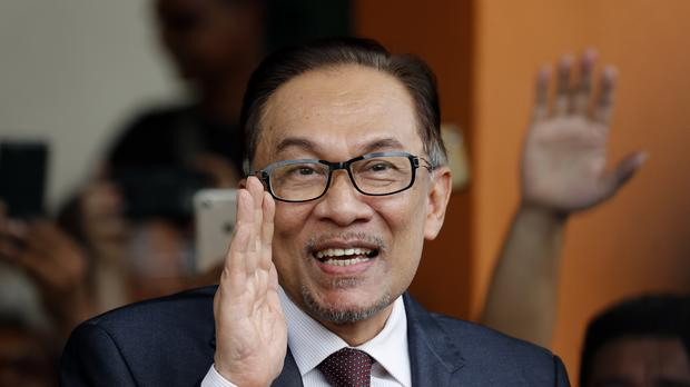 Anwar Ibrahim waves to supporters as he leaves a hospital in Kuala Lumpur, (Vincent Thian/AP)