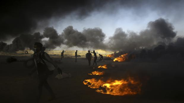 Palestinian protesters burn tires during a protest at the Gaza Strip's border with Israel, east of Khan Younis (AP)