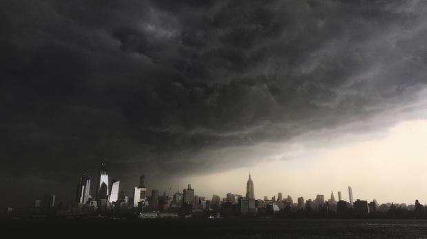Storm clouds gather over New York city seen from the Hudson River (AP)