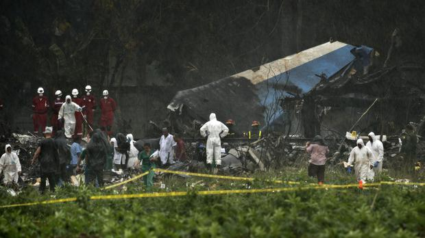 Rescue teams search through the wreckage site of the Boeing 737 (Ramon Espinosa/AP)