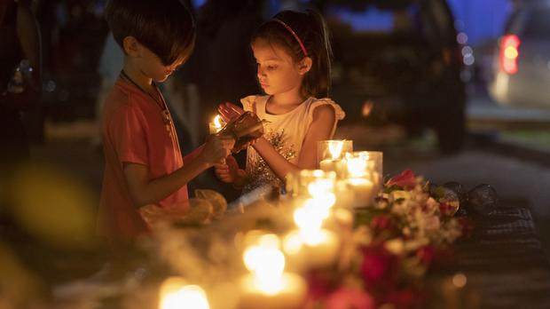 Lucrecia Martinez, seven, and her brother Luciano, nine, light candles during a vigil held in the wake of the shooting (Stuart Villanueva/The Galveston County Daily News/AP/PA)