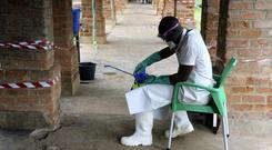 A health care worker wears virus protective gear at a treatment centre in Bikoro (John Bompengo/AP)