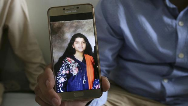 Abdul Aziz Sheikh, father of Sabika Sheikh, shows a picture of his daughter in Karachi, Pakistan (Fareed Khan/AP)