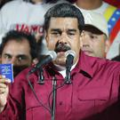 Venezuela's President Nicolas Maduro, holding a copy of the country's constitution, addresses supporters at the presidential palace in Caracas (AP)