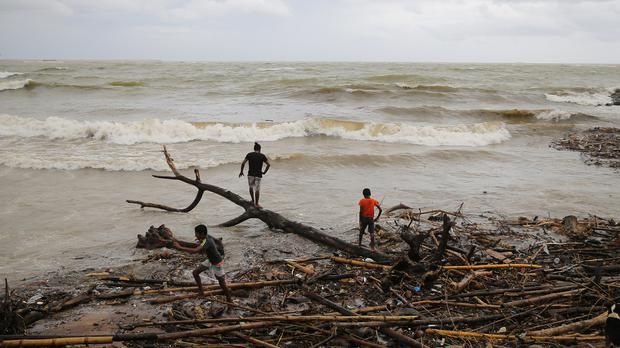 Sri Lankans look for recyclable material washed ashore in Colombo after heavy rain (Eranga Jayawardena/AP)