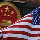 An American flag is flown next to the Chinese national emblem