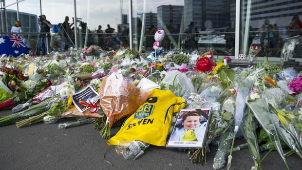 A photo of a victim of flight MH17 lays next to flowers at Schiphol airport in Amsterdam (Patrick Post/AP)