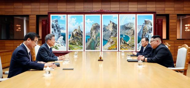 ON/OFF: South Korean President Moon Jae-in (left) talks with North Korean leader Kim Jong Un (right) before their meeting yesterday in the Korean DMZ. Photo: AFP/Getty