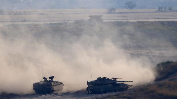 Israeli tanks take up positions along the border with the Gaza strip (AP)