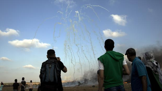 Teargas canisters fired by Israeli troops fall over Palestinian protesters during a protest at the Gaza Strip's border with Israel (Khalil Hamra/AP)