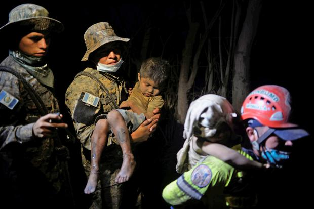 A soldier takes a rescued child covered with ash to hospital