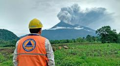 A man watches as Volcano Fuego erupts. Photo: Getty