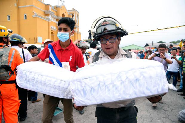 Volunteer firefighters carry the coffins of two children who were killed by El Fuego volcano in Guatemala. Photo: AFP
