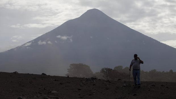 A man on the barren terrain near the Volcan de Fuego (Moises Castillo/AP)