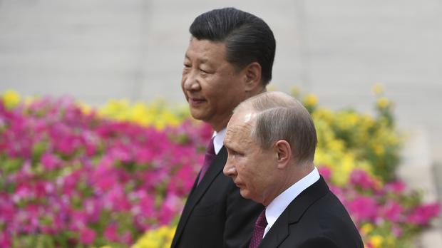 Vladimir Putin reviews a military honour guard with Chinese president Xi Jinping (AP)