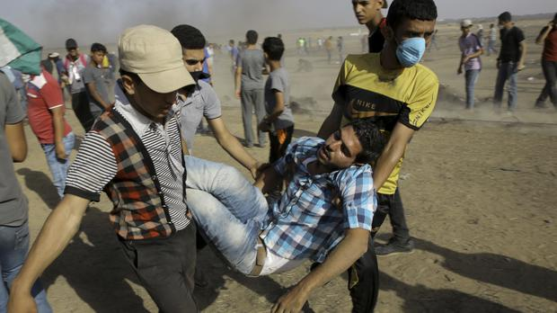 Palestinian medics and protesters evacuate a wounded youth (Adel Hana/AP)