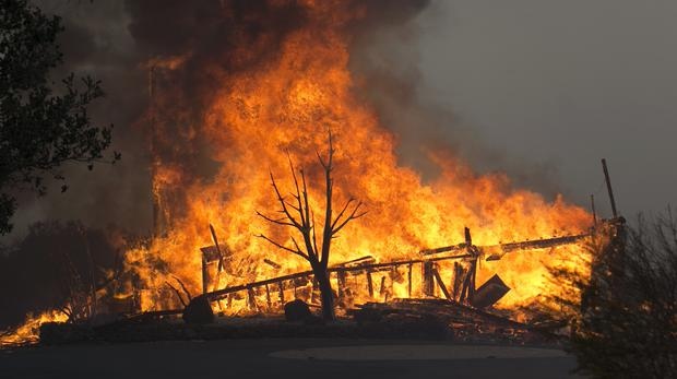 Flames from a wildfire consume a home near Napa, California (Rich Pedroncelli/AP)