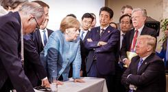 TOUGH TALK: From left, British Prime Minister Theresa May, Larry Kudlow, director of the National Economic Council, French President Emmanuel Macron, German Chancellor Angela Merkel, Yasutoshi Nishimura, Japanese deputy chief cabinet secretary, Japanese Prime Minister Shinzo Abe, unidentified, John Bolton, US national security adviser, US President Donald Trump, participate in a working session at the G-7 summit in Charlevoix, Canada, in this photo taken by Angela Merkel's official photographer. Photo: Jesco Denzel, courtesy Angela Merkel's Instagram account