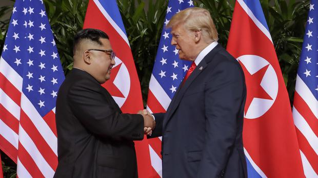 Donald Trump shakes hands with Kim Jong Un at the Capella resort on Sentosa Island (Evan Vucci/AP)