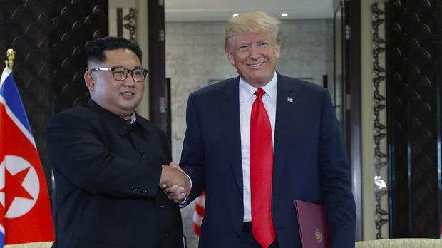 Kim Jong Un and Donald Trump shake hands after signing a document at a summit in Singapore (Evan Vucci/AP)