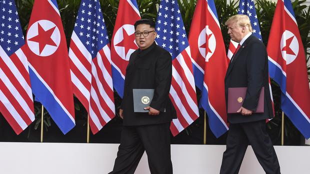 Kim Jong Un and Donald Trump with the documents they signed on Tuesday (Anthony Wallace/pool/AP)