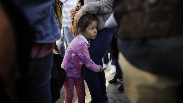 Nicole Hernandez, of the Mexican state of Guerrero, holds on to her mother as they wait with other families to request political asylum in the US, across the border in Tijuana, Mexico (Gregory Bull/AP)