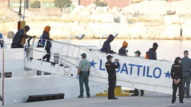 Migrants leave the Italian coastguard vessel Dattilo (Alberto Saiz/AP)