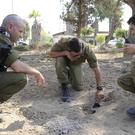 Israeli soldiers inspect a missile launched from the Gaza Strip (Tsafrir Abayov/AP)