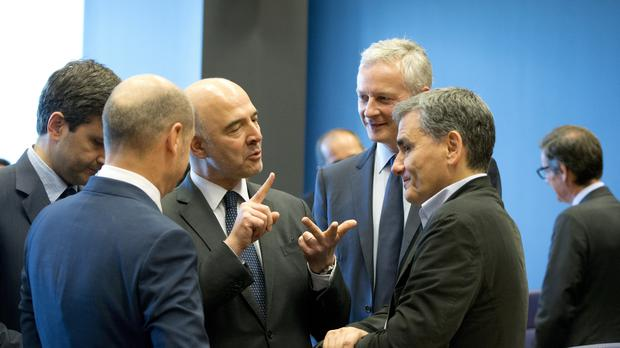 Greek finance minister Euclid Tsakalotos speaks with European Commissioner for Economic and Financial Affairs Pierre Moscovici during a meeting of eurogroup finance ministers (Virginia Mayo/AP)