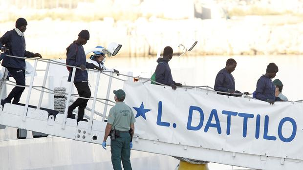 Migrants descend the Italian coast guard vessel Dattilo upon arrival at the eastern port of Valencia, Spain (Alberto Saiz/AP)