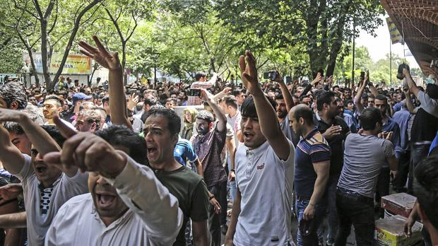 A group of protesters chant slogans at the old grand bazaar in Tehran (ILNA via AP)