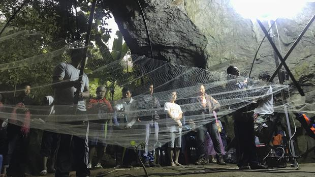 A group of locals and relatives perform a ritual calling for those who are missing at the entrance of the cave in Thailand (Tassanee Vejpongsa/AP)