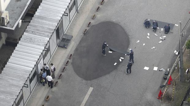 Investigators work at an elementary school after a man fatally shot a security guard in Toyama (AP)
