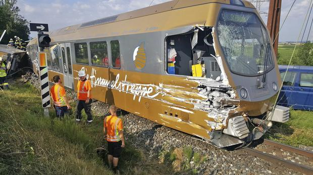 Rescues workers stand beside a damaged train near St Poelten (AP)