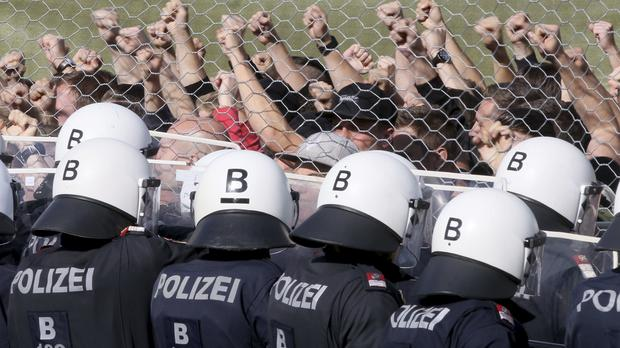 Austrian police stand behind a fence as they practice the protection of the border (Ronald Zak/AP)