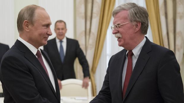 Russian President Vladimir Putin shakes hands with US security adviser John Bolton (AP)
