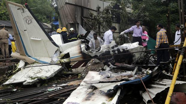 Rescuers stand amid the wreckage of the plane that crashed in Mumbai, India (Rajanish Kakade/AP)