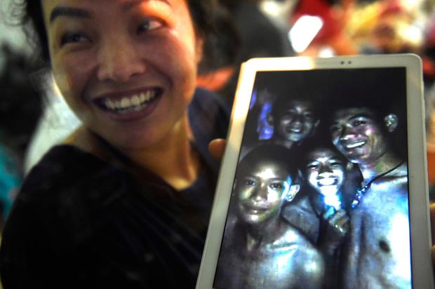 Joyful family members celebrate as they view a photo of the missing boys taken by rescue divers