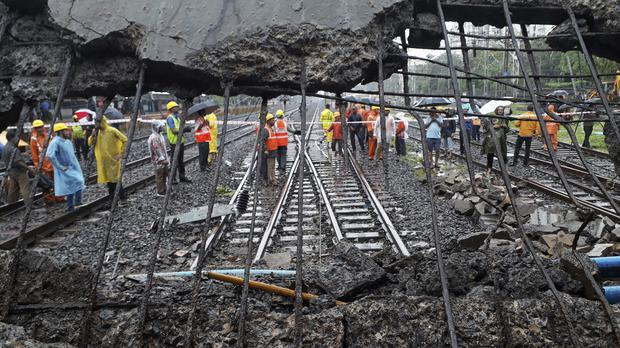 Rescue workers at the site of a pedestrian bridge that collapsed at a railway station in Mumbai, India (Rafiq Maqbool/AP)